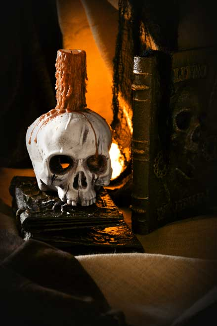 A scary skull with a candle on it, sits on magic books.
